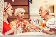 Good-looking old women being involved in gambling card game. During active game. Good-looking old women being involved in gambling card game while sitting in a stock photo