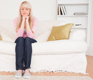 Good looking pensive female sitting on a sofa Royalty Free Stock Image