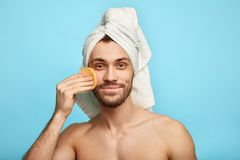 Good looking pleasant man wiping face with cosmetic sponge stock images
