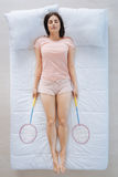 Good looking pleasant woman sleeping with badminton rackets. Favourite game. Good looking pleasant young woman holding badminton rackets and dreaming about Stock Photo