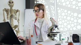 Good-looking pleasant young doctor in glasses working with microscope and computer in the clinic cabinet
