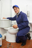 Good looking plumber repairing toilet Stock Photos
