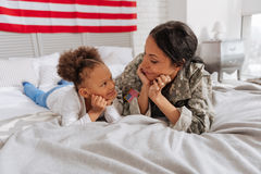 Good looking positive ladies relaxing in bedroom. Like best friends. Amazing lively beautiful mother and her cute daughter chatting together while spending the stock image