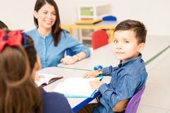 Good looking preschool student. Portrait of a handsome Hispanic preschool student sitting at class and working on a writing assigment stock photography