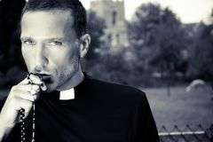 Good looking priest kisses his rosary with church, field and alpaca in background royalty free stock photo