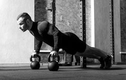Good looking professional sportsman working out. Developing strength. Good looking professional well built sportsman working out in the gym and developing his Royalty Free Stock Photography