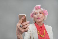 Good looking senior blond woman posing at camera royalty free stock photography