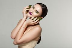 Good looking serious girl with avocado looking at the camera royalty free stock image