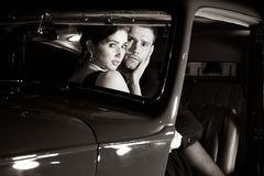 Good looking couple, handsome man in suit, beatiful woman in red dress, are discovered embracing in vintage car stock photos
