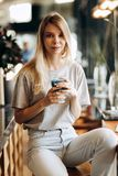 A good looking slim blonde girl,wearing casual style, sits on the chair and holds a cup of coffee in a cozy coffee shop royalty free stock photos