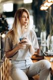 A good looking slim blonde girl,wearing casual style, sits on the chair and holds a cup of coffee in a cozy coffee shop stock images