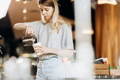 A good looking slim blonde with long hair,dressed in casual outfit,is cooking coffee in a modern coffee shop. Process of stock images
