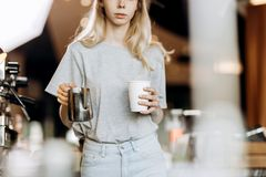 A good looking slim blonde with long hair,dressed in casual outfit,is cooking coffee in a modern coffee shop. Process of royalty free stock photos
