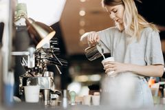 A good looking slim blonde with long hair,dressed in casual outfit,is cooking coffee in a modern coffee shop. Process of stock photography