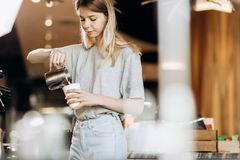 A good looking slim blonde with long hair,dressed in casual outfit,is cooking coffee in a modern coffee shop. Process of royalty free stock image