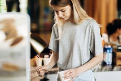 A good looking slim blonde with long hair,dressed in casual outfit,is cooking coffee in a modern coffee shop. Process of stock image