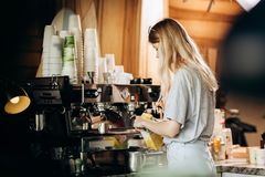A good looking slim blonde with long hair,dressed in casual outfit,is cooking coffee in a modern coffee shop. Process of royalty free stock images