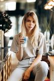 A good looking slim girl,wearing casual style, sits on the chair and holds a cup of coffee in a cozy coffee shop. royalty free stock photos