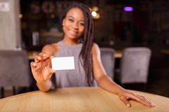 An Afro-American woman is showing a business card royalty free stock photos