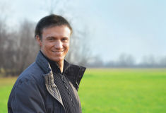 Good looking smiling man outdoors. Handsome young man smiling in a green field Stock Image