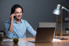 Good looking smiling young man speaking on cellphone . Royalty Free Stock Images
