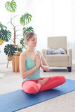 Good-looking sportive girl meditating while sitting on yoga mat Royalty Free Stock Image