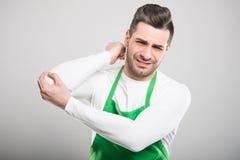 Good looking supermarket employer holding elbow like hurting. On white background Stock Photos