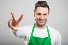 Good looking supermarket employer posing showing peace gesture. On white background Stock Image