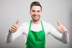 Good looking supermarket employer showing like gesture. Good looking supermarket employer showing double like or thumb up gesture and smiling on white background Stock Photography
