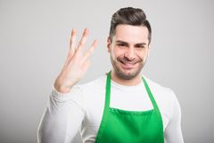 Good looking supermarket employer showing number three. And smiling on white background Stock Images