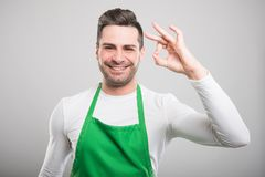 Good looking supermarket employer showing ok gesture. And smiling on white background Royalty Free Stock Photography