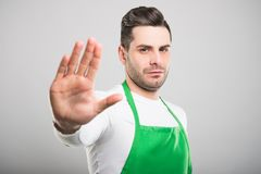 Good looking supermarket employer showing stop gesture. With palm on white background Royalty Free Stock Photos