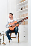 Good looking talented man holding the guitar Stock Photos