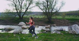 Good looking two women with a fit bodies running hard in the middle of mountain road with amazing landscape around river