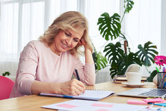 Good-looking woman with beautiful smile writing in notebook whil Royalty Free Stock Images