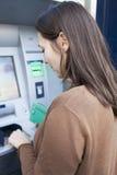 Woman enters PIN number at cash mashine Stock Photos