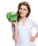 Good looking woman of European appearance holding a head of cabbage in her hand, healthy food concept Stock Photos