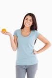Good looking woman holding an orange Royalty Free Stock Photos