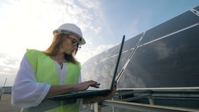 Attractive woman is operating her laptop while being near a solar construction