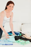Good looking woman packing her suitcase Stock Images