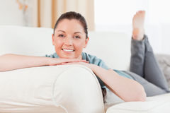 Good looking woman posing while lying on a sofa Stock Image