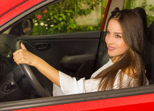 Good looking woman in red car, wearing a white blouse while she is driving Royalty Free Stock Image