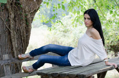 Good looking woman sitting on a wooden table. Good looking woman wearing white shirt, jean pants and heels sitting on a wooden table outside in nature, facing Stock Image