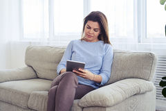 Good-looking woman working in laptop while sitting on sofa Royalty Free Stock Photo