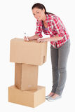 Good looking woman writing on cardboard boxes Royalty Free Stock Images