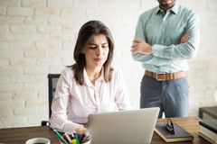 Woman working while being supervised. Good looking women working in a computer and being supervised by her boss while she looks uncomfortable Stock Photo