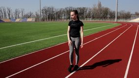 Good looking young active fit girl workout upper body leg stretch exercise squat to warm up tone muscles at big stadium. Good looking young active fit girl stock video