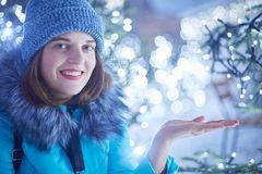 Good looking young adorable woman catches snowflakes, dressed in warm winter clothes, stands outdoor, enjoys winter time, spends t stock photos