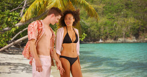 Good looking young couple holding hands on tropical beach. Royalty Free Stock Photo