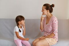Good looking young European language therapist teaching small female child right sounds pronunciation, working on speech